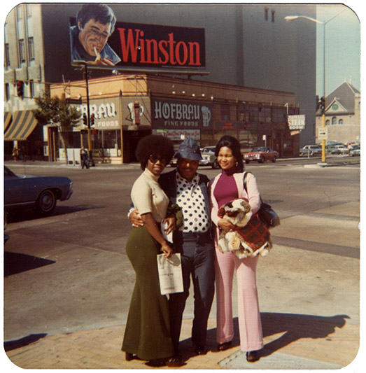 Unknown folks pose for photo at corner of Broadway and West Grand in downtown Oakland, circa 1973.